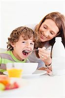 Mother feeding son cereal Stock Photo - Premium Royalty-Freenull, Code: 649-05949951