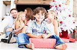 Boy sitting with wrapped Christmas gift Stock Photo - Premium Royalty-Freenull, Code: 649-05949991