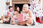 Girl sitting with wrapped Christmas gift Stock Photo - Premium Royalty-Freenull, Code: 649-05949992