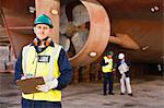 Worker carrying clipboard on dry dock Stock Photo - Premium Royalty-Freenull, Code: 649-05950055