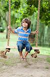 Smiling boy sitting in tree swing Stock Photo - Premium Royalty-Freenull, Code: 649-05950113
