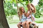 Smiling girls sitting in tree swing Stock Photo - Premium Royalty-Freenull, Code: 649-05950114