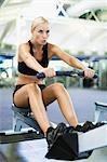 Woman using rowing machine in gym Stock Photo - Premium Royalty-Freenull, Code: 649-05950189