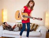 Girl playing guitar in living room Stock Photo - Premium Royalty-Freenull, Code: 649-05950575