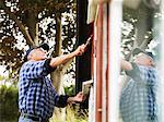Older man painting side of house Stock Photo - Premium Royalty-Free, Artist: Cultura RM, Code: 649-05950624