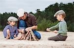 Father and sons making a bonfire on beach Stock Photo - Premium Royalty-Free, Artist: Blend Images, Code: 614-05955513