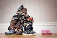 family shoes - Large pile of boy's shoes beside one pair of girl's shoes Stock Photo - Premium Royalty-Freenull, Code: 614-05955603