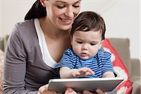 Mother and baby looking at digital tablet Stock Photo - Premium Royalty-Freenull, Code: 614-05955627