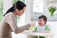 Mother feeding crying baby son Stock Photo - Premium Royalty-Freenull, Code: 614-05955650