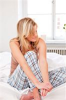 Woman sitting on bed in pajamas Stock Photo - Premium Royalty-Freenull, Code: 698-05956121