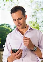 Man with head phones and mobile talking Stock Photo - Premium Royalty-Freenull, Code: 698-05957139