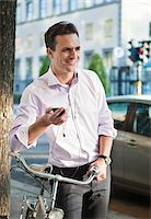 Man with mobile phone and headset holding bicycle Stock Photo - Premium Royalty-Freenull, Code: 698-05957167