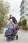 Mother pulling baby (2-3) stroller and looking at camera Stock Photo - Premium Royalty-Free, Artist: Ikon Images, Code: 698-05957766