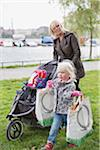 Child carrying bags while woman pushing cart Stock Photo - Premium Royalty-Free, Artist: Siephoto, Code: 698-05957787
