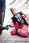 Boy working on flat tire with jack Stock Photo - Premium Royalty-Free, Artist: Science Faction, Code: 698-05959035