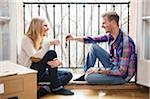 Man giving house keys to girlfriend while sitting in balcony Stock Photo - Premium Royalty-Free, Artist: ableimages, Code: 698-05959341