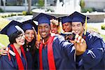 Graduates taking picture of themselves Stock Photo - Premium Royalty-Free, Artist: Blend Images, Code: 635-05971472
