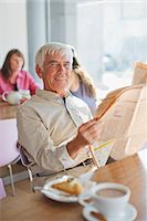 Man reading newspaper in cafe Stock Photo - Premium Royalty-Freenull, Code: 635-05971700