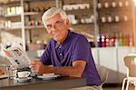 Man reading newspaper in cafe Stock Photo - Premium Royalty-Freenull, Code: 635-05971729