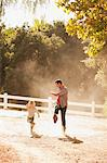 Father and son kicking up dust on dirt road Stock Photo - Premium Royalty-Freenull, Code: 635-05971749