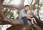 Father and son hugging in tree Stock Photo - Premium Royalty-Free, Artist: Raimund Linke, Code: 635-05971754