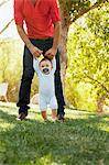 Father helping baby walk outdoors Stock Photo - Premium Royalty-Free, Artist: Blend Images, Code: 635-05971803