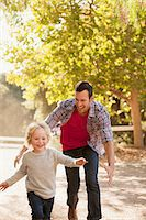 Father chasing son on dirt road Stock Photo - Premium Royalty-Freenull, Code: 635-05971813