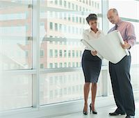 Business people reading blueprints in office Stock Photo - Premium Royalty-Freenull, Code: 635-05971912