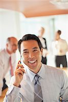 Businessman talking on cell phone in office Stock Photo - Premium Royalty-Freenull, Code: 635-05971937