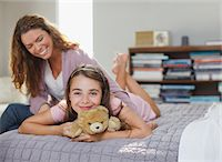 Mother and daughter relaxing on bed Stock Photo - Premium Royalty-Freenull, Code: 635-05971990