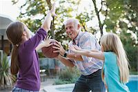Older man playing basketball with granddaughters Stock Photo - Premium Royalty-Freenull, Code: 635-05971991