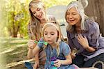 Three generations of women blowing bubbles Stock Photo - Premium Royalty-Free, Artist: Blend Images, Code: 635-05972018