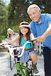 Older man helping granddaughter ride bicycle Stock Photo - Premium Royalty-Free, Artist: Blend Images, Code: 635-05972024
