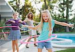 Mother and daughters hula hooping outdoors Stock Photo - Premium Royalty-Freenull, Code: 635-05972092