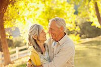 Smiling older couple hugging outdoors Stock Photo - Premium Royalty-Freenull, Code: 635-05972107