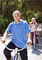 Smiling older couple riding bicycles Stock Photo - Premium Royalty-Freenull, Code: 635-05972126