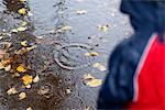 Girl watching rain drops in puddle Stock Photo - Premium Royalty-Free, Artist: Cultura RM, Code: 635-05972279