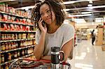 Woman talking on cell phone in supermarket Stock Photo - Premium Royalty-Free, Artist: Blend Images, Code: 635-05972310
