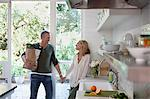 Couple holding hands in kitchen Stock Photo - Premium Royalty-Free, Artist: Minden Pictures, Code: 635-05972337