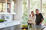 Couple watching television in kitchen Stock Photo - Premium Royalty-Free, Artist: Tim Hurst, Code: 635-05972360