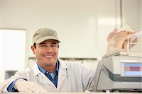 Butcher weighing meat behind counter Stock Photo - Premium Royalty-Freenull, Code: 635-05972368