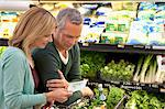 Couple checking grocery list in supermarket Stock Photo - Premium Royalty-Free, Artist: Aurora Photos, Code: 635-05972385
