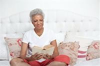 Older woman reading Bible on bed Stock Photo - Premium Royalty-Freenull, Code: 635-05972425