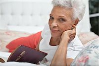 Older woman reading Bible in bed Stock Photo - Premium Royalty-Freenull, Code: 635-05972442