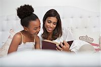 Mother and daughter reading Bible together Stock Photo - Premium Royalty-Freenull, Code: 635-05972462