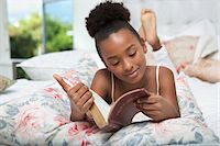 Girl reading Bible in bed Stock Photo - Premium Royalty-Freenull, Code: 635-05972472