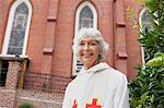 Smiling reverend standing outside church Stock Photo - Premium Royalty-Free, Artist: Robert Harding Images, Code: 635-05972495