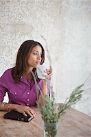 Woman having cup of coffee at table Stock Photo - Premium Royalty-Freenull, Code: 635-05972496