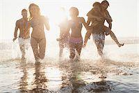 Friends running in waves on beach Stock Photo - Premium Royalty-Freenull, Code: 635-05972562