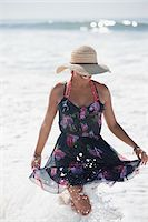 Woman walking in waves at beach Stock Photo - Premium Royalty-Freenull, Code: 635-05972573